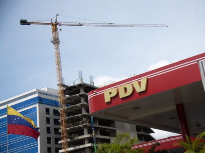 CARACAS, VENEZUELA - JUNE 01: View of PDVSA logo and the Venezuelan flag at a gas station in Las Mercedes on June 1, 2020 in Caracas, Venezuela. After 77 days, Maduro Administration eases the restrictions against COVID-19, allowing certain activities to reopen. From today, an official limit has been set …