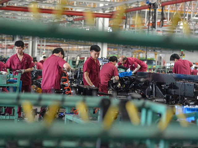 Employees work on a truck assembly line at a factory in Fuyang in China's eastern Anhui province on July 16, 2020. - China's economy returned to growth in the second quarter, rebounding more strongly than expected from a historic contraction caused by the coronavirus outbreak, official data showed on July …