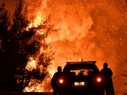 TOPSHOT - Firefighters stand near a pine forest wildfire fanned by strong winds near the village of Athikia, in Peloponnese area near Corinth late on July 22, 2020. - Greek authorities evacuated five settlements as a precaution. Summer fires are frequent in Greece, with temperatures regularly over 30 degrees Celsius …