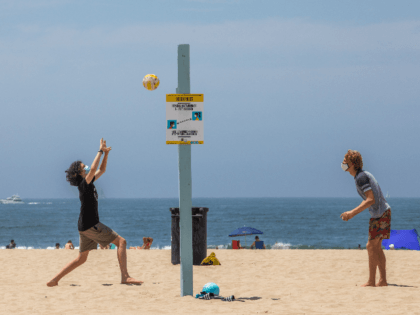 Men wearing face masks play volleyball on the beach amid the severe heat wave in Venice, California on August 15, 2020. - The worst heat wave in several years caused rolling blackouts August 14, 2020 due to power shortages and is setting up dangerous conditions across California. (Photo by Apu …
