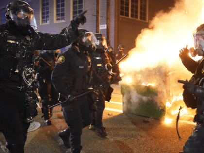 Portland police officers push protesters past a dumpster fire during a dispersal from in front of the Immigration and Customs Enforcement (ICE) detention facility in the early morning on August 21, 2020 in Portland, Oregon. For the second night in a row city police and federal officers clashed with protesters …