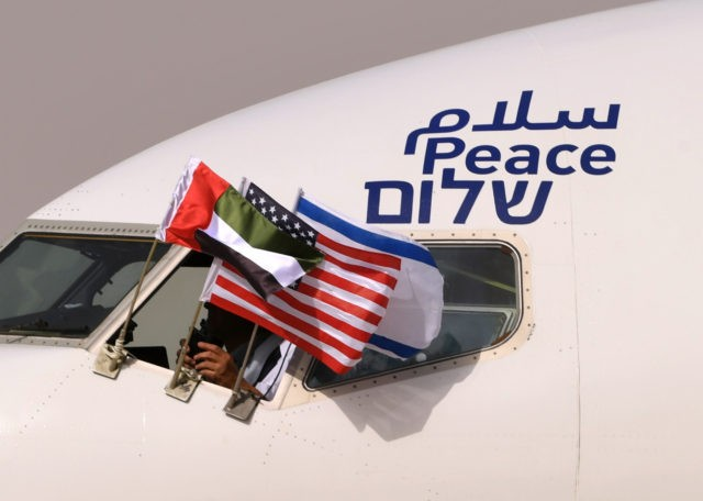 "TOPSHOT - The Emirati, Israeli and US flags are picture attached to an air-plane of Israel's El Al, adorned with the word ""peace"" in Arabic, English and Hebrew, upon it's arrival at the Abu Dhabi airport in the first-ever commercial flight from Israel to the UAE, on August 31, 2020. …"