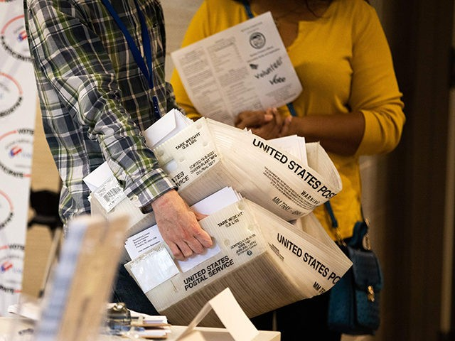 An absentee ballot election worker consolidates a large stack of absentee ballot applications at the Mecklenburg Board of Elections office in Charlotte, North Carolina on September 4, 2020. - The US election is officially open: North Carolina on September 4, 2020 launched vote-by-mail operations for the November 3 contest between …