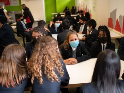 Year eight pupils wear face masks as a precaution against the transmission of the novel coronavirus as they chat before collecting their food in the dining room of Moor End Academy in Huddersfield, northern England on September 11, 2020. - Millions of children across England have returned to school after …
