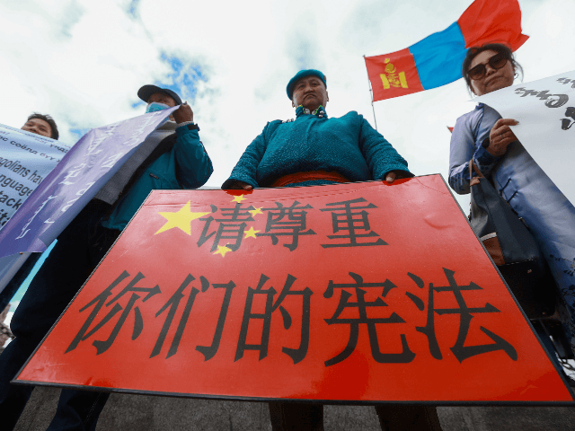 "A Mongolian man holds a protest banner in the shape of the Chinese flag which reads ""Respect your constitution"" during a protest against China's plan to introduce Mandarin-only classes at schools in the Chinese province of Inner Mongolia, at Sukhbaatar Square in Ulaanbaatar, the capital of Mongolia on September 15, …"