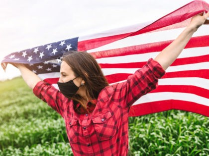 US flag is flying in hands of young woman in protective mask on her face