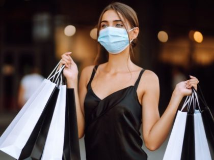Young woman in protective sterile medical mask on her face with shopping bags enjoying in shopping.