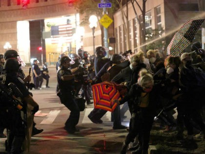 """ROCHESTER, NEW YORK - SEPTEMBER 04: Police officers clash with demonstrators as they attempt to clear the streets after a march for Daniel Prude on September 04, 2020 in Rochester, New York. Prude died after being arrested on March 23, by Rochester police officers who had placed a """"spit hood"""" …"""