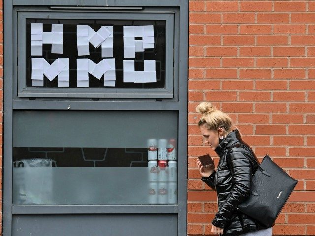 A woman walks past messages pasted inside the windows of the Cambridge Halls student accommodation, for students at Manchester Metropolitan University, in Manchester, north-west England on September 28, 2020, as many students live in a temporary lock-down in a bid to reduce the spread of the novel coronavirus covid-19 on …