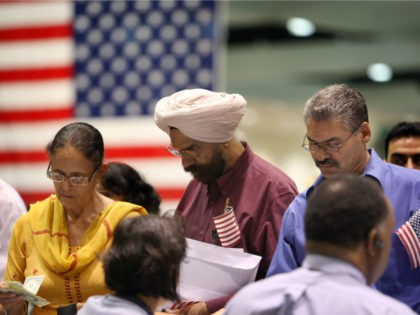 Amrik Sidhu (C) and his wife Harjinder Sidhu (L), both Sikhs from India, apply for their passports after gaining US citizenship as 18,418 people are sworn in as US citizens during naturalization ceremonies at the Los Angeles Convention Center on August 28, 2008 in Los Angeles, California. Immigrants, especially Latinos, …