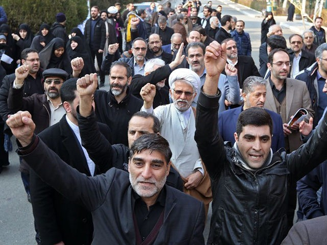 Supporters of the Basij, a militia loyal to the Islamic republic's establishment, chant anti-US slogans during a memorial for the victims of the Ukraine plane crash in University of Tehran on January 14, 2020. - Iran announced its first arrests over the shooting down of a Ukrainian airliner last week, …