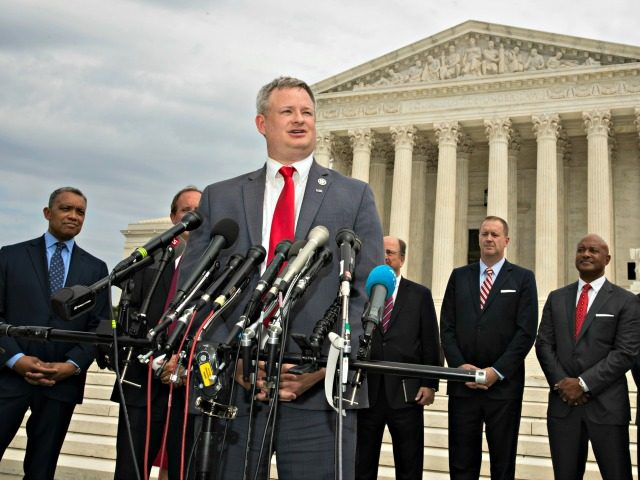 South Dakota Attorney General Jason Ravnsborg with a bipartisan group of state attorneys general speaks to reporters in front of the U.S. Supreme Court in Washington, Monday, Sept. 9, 2019. A bipartisan coalition of 48 states along with Puerto Rico and the District of Columbia said Monday it is investigating …