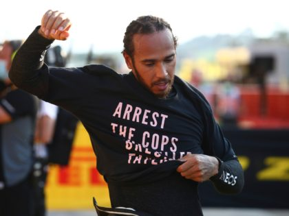 Mercedes driver Lewis Hamilton of Britain puts on a t-shirt after winning the Formula One Grand Prix of Tuscany, at the Mugello circuit in Scarperia, Italy, Sunday, Sept. 13, 2020. (Bryn Lennon, Pool via AP)