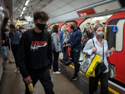 Commuters wearing a face mask or covering due to the COVID-19 pandemic, walk past a London underground tube train at Victoria station, during the evening 'rus hour' in central London on September 23, 2020.. - The UK on Wednesday reported 6,178 new coronavirus cases, a marked jump in the daily …