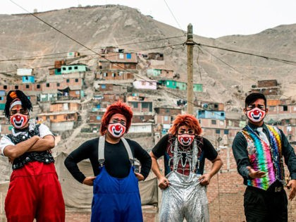 Clowns wearing face masks pose for a picture before performing at Puente Piedra district, in the northern outskirts of Lima on August 03, 2020, during the COVID-19 pandemic. - Due to the coronavirus pandemic, circuses in Peru remain closed, leading this group of clowns traveling in their mototaxi circus to …