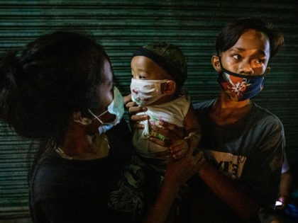 MANILA, PHILIPPINES - AUGUST 7: A homeless teenage couple carry their months-old infant as they queue to receive free meals from volunteers on August 7, 2020 in Caloocan, Metro Manila, Philippines. The Philippine economy suffered its worst slump on record in the second quarter, falling into recession for the first …