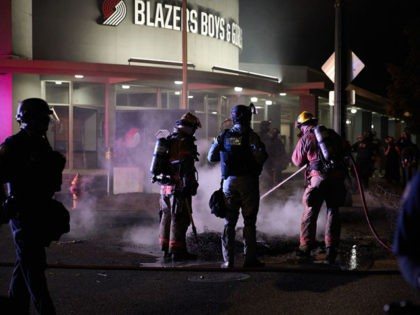 Firemen extinguish a fire set by protestors in front of the North Precinct Police building in Portland, Oregon on September 6, 2020. - Protestors are marching for an end to racial inequality and police violence. Aaron Danielson, 39, a supporter of a far-right group called Patriot Prayer, was fatally shot …