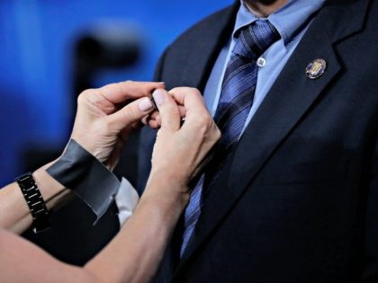 A technician adjusts a microphone on New Jersey Sen. Ray Lesniak before the start of a Democratic gubernatorial primary debate, Thursday, May 11, 2017, in Newark, N.J. (AP Photo/Julio Cortez, Pool)