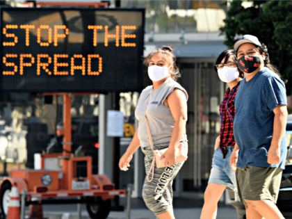 FILE - Pedestrians wear masks as they walk in front of a sign reminding the public to take steps to stop the spread of coronavirus, Thursday, July 23, 2020, in Glendale, Calif. Los Angeles County is seeing some hopeful signs amid the coronavirus surge. The county reported Wednesday that COVID-19 …