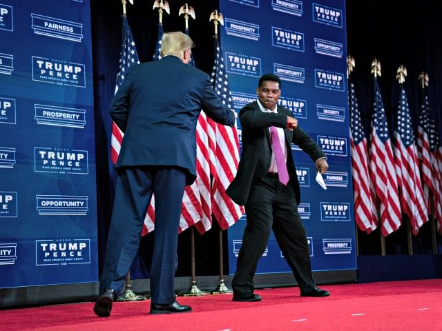 President Donald Trump greets former running back Herschel Walker before speaking at a campaign event at the Cobb Galleria Centre, Friday, Sept. 25, 2020, in Atlanta. (AP Photo/Evan Vucci)
