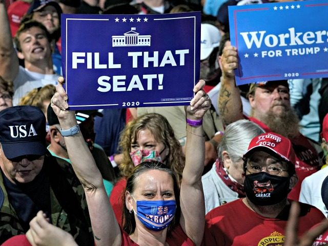 """NEWPORT NEWS, VA - SEPTEMBER 25: A woman holds up a """"Fill That Seat"""" sign before the arrival of President Donald Trump during a campaign rally at Newport News/Williamsburg International Airport on September 25, 2020 in Newport News, Virginia. President Trump is scheduled to announce his nomination to the Supreme …"""