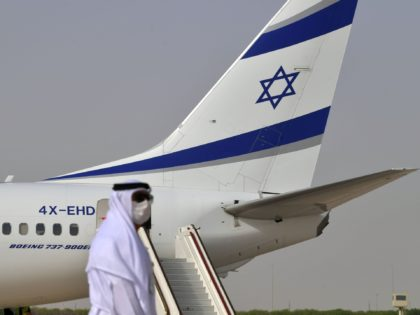 An Emirati official stands near an air-plane of El Al, which carried a US-Israeli delegation to the UAE following a normalisation accord, upon it's arrival at the Abu Dhabi airport in the first-ever commercial flight from Israel to the UAE, on August 31, 2020. - A US-Israeli delegation including White …