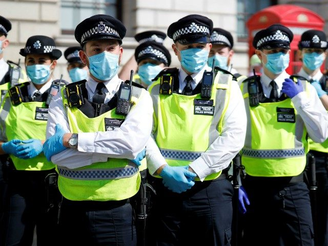 "Police officers wearing face masks and gloves due to the COVID-19 pandemic, stand on duty as activists from the climate protest group Extinction Rebellion demonstrate in Parliament Square in London on September 2, 2020, on the second day of their new season of ""mass rebellions"". - Climate protest group Extinction …"