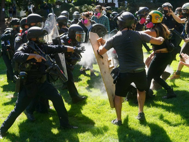 Federal officers disperse a crowd of anti-police protesters after the group chased right wing groups out of downtown and then continued protesting in Terry Schrunk Plaza on August 22, 2020 in Portland, Oregon. For the second Saturday in a row, right wing groups gathered in downtown Portland, sparking counter protests …