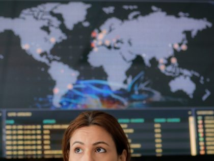 A woman sits backdropped by a real time cyber attacks world map, at the headquarters of Bitdefender in Bucharest, Romania, Wednesday, June 28, 2017. A new, highly virulent strain of malicious ransom software that is crippling computers globally appears to have been sown in Ukraine, where it badly hobbled much …