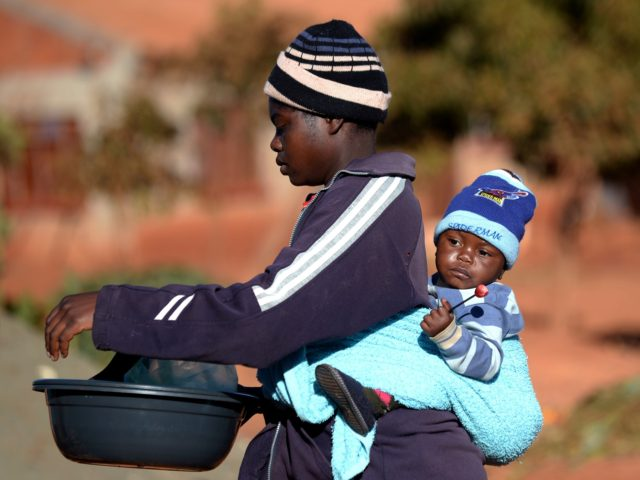"""A woman carries her baby on her back as she shops at a market in Domboshava, 60km north of Harare, on August 1, 2013. Vote counting is under way on August 1 after Zimbabwe's tightly fought election which regional observers said was """"orderly and fair"""" despite charges of vote-rigging by …"""