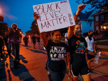 A protester holds a Black Lives Matter sign during a demonstration against the shooting of Jacob Blake in Kenosha, Wisconsin on August 26, 2020. - Outrage continued to spread after Kenosha, Wisconsin police shot Jacob Blake multiple times in the back point-blank in front of his children in the Midwestern …