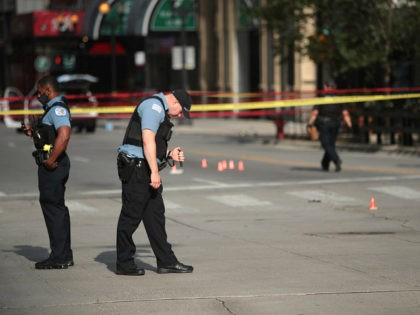 CHICAGO, ILLINOIS - AUGUST 10: Police investigate where a shooting took place on Michigan Ave. hours after the city suffered from widespread looting and vandalism, on August 10, 2020 in Chicago, Illinois. Police made several arrests during the night of unrest and recovered at least one firearm. (Photo by Scott …