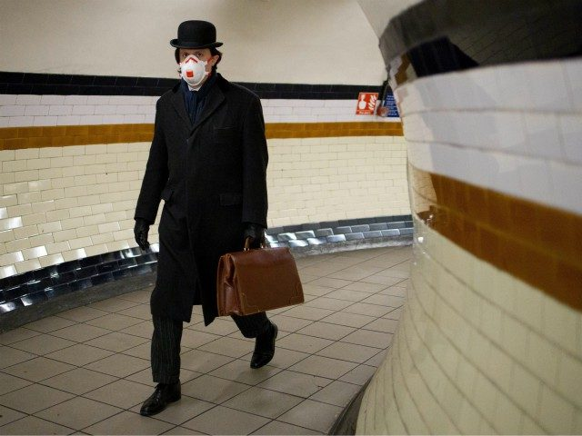 """A commuter wears a face mask as a precautionary measure against the novel coronavirus COVID-19 as he walks at Lambeth North station to a Bakerloo line train on the London Underground on April 2, 2020. - Prime Minister Boris Johnson said Britain would """"massively increase testing"""" amid a growing wave …"""