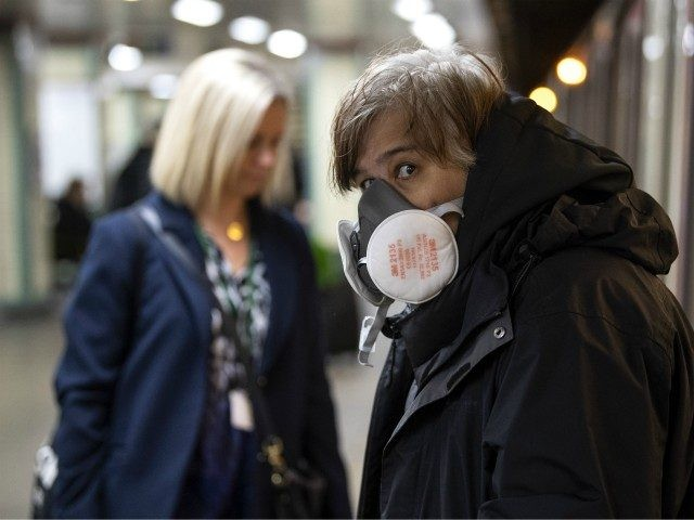 LONDON, ENGLAND - MARCH 23: A Commuters wearing a face protection mask travels on the underground on March 23, 2020 in London, United Kingdom. Coronavirus (COVID-19) pandemic has spread to at least 182 countries, claiming over 10,000 lives and infecting hundreds of thousands more. (Photo by Justin Setterfield/Getty Images)