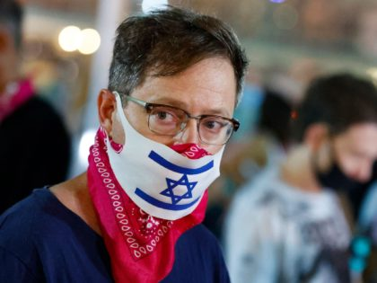An Israeli man wearing a face mask with the national flag, takes part in a demonstration against the Prime Minister and an imminent and unprecedented second nationwide lockdown to tackle a spike in coronavirus, in the coastal city of Tel Aviv, on September 17, 2020. - The measures will be …