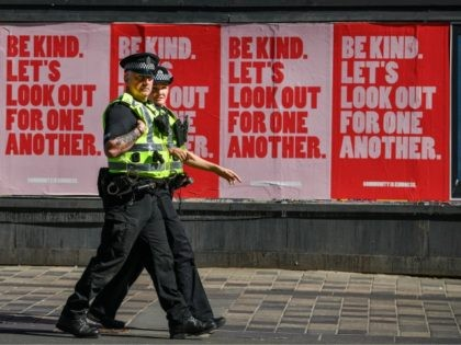 GLASGOW, SCOTLAND - MAY 06: Two police officers walk past posters on Sauchiehall Street during the coronavirus lockdown on May 6, 2020 in Glasgow, Scotland. The country continues quarantine measures intended to curb the spread of Covid-19, but the infection rate is falling, and government officials are discussing the terms …