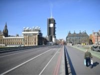 TOPSHOT - A picture shows the Houses of Parliament (L) at the end of an empty Westminster Bridge with one pedestrian on the pavement in central London in the morning on March 24, 2020 after Britain ordered a lockdown to slow the spread of the novel coronavirus. - Britain was …