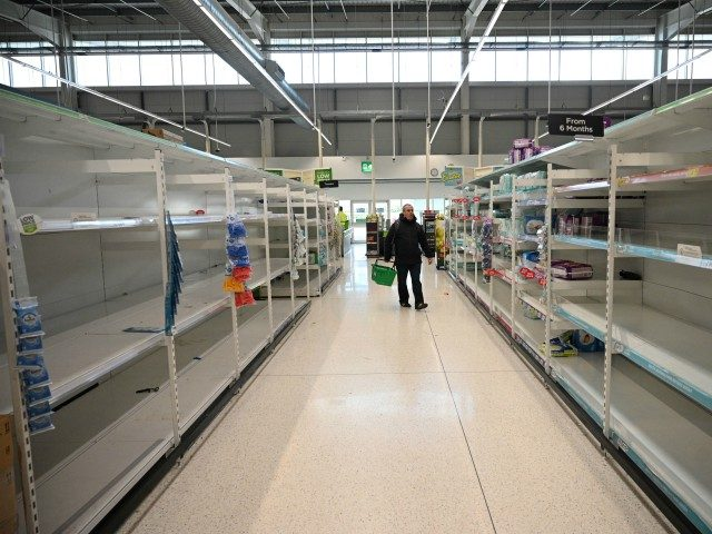 A shopper walks past empty toilet roll shelves amidst the novel coronavirus COVID-19 pandemic, in Manchester, northern England on March 20, 2020. - The British prime minister urged people in his daily press conference on March 19 to be reasonable in their shopping as supermarkets emptied out of crucial items …