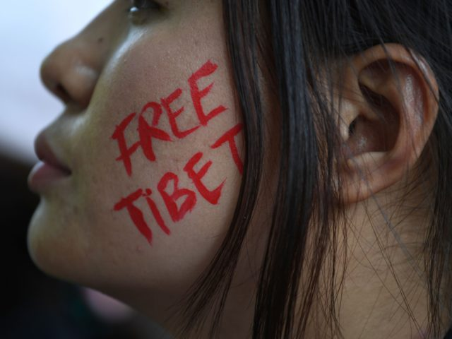"TOPSHOT - An exiled Tibetan activist face is painted with the slogan ""Free Tibet"" during a protest marking the 60th anniversary of the 1959 Tibetan uprising against Chinese rule in the Indian capital New Delhi on March 10, 2019. - Crowds gathered March 10 at the Dalai Lama's temple in …"