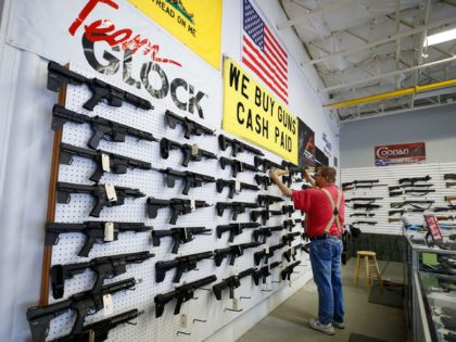 A worker restocks AR-15 guns at Davidson Defense in Orem, Utah on March 20, 2020. - Gun stores in the US are reporting a surge in sales of firearms as coronavirus fears trigger personal safety concerns. (Photo by GEORGE FREY / AFP) (Photo by GEORGE FREY/AFP via Getty Images)