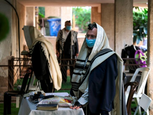 "Ultra-Orthodox Jewish men, wearing a protective face masks due to the COVID-19 coronavirus pandemic and ""Talit"" prayer shawl, keep a two-metre distance as they pray along a street outside a synagogue in the ultra-Orthodox city of Bnei Brak, near Tel Aviv on September 6, 2020. - Israel, next week, is …"