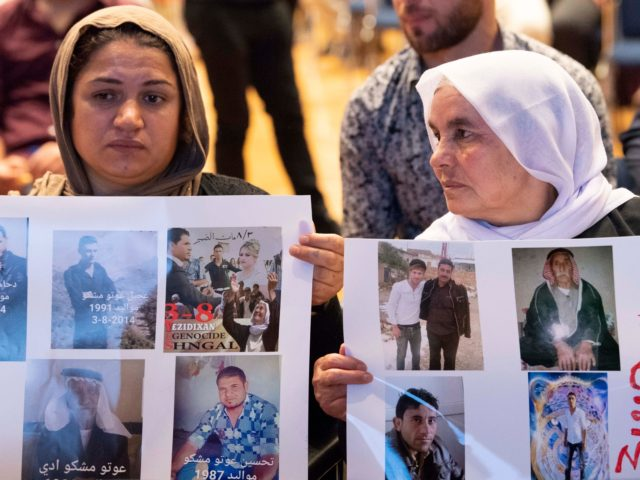 Yazidi women hold up pictures of missed relatives during a commemoration ceremony in Stuttgart, southern Germany, on August 3, 2019. - The Central Yazidi Council in Germany commemorates the 5th anniversary of the genocide of the Yazidi in August 2014 when fighters of the Islamic State (IS) killed thousands of …