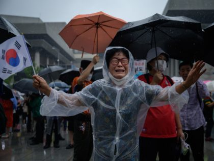 TOPSHOT - A woman weeps as members of pro-US conservative right-wing and religious christian groups wave flags and shout slogans during an anti-government rally in the central Gwanghwamun area of Seoul on August 15, 2020. - Thousands of anti-government protestors defied official social distancing warnings to hold rallies as South …