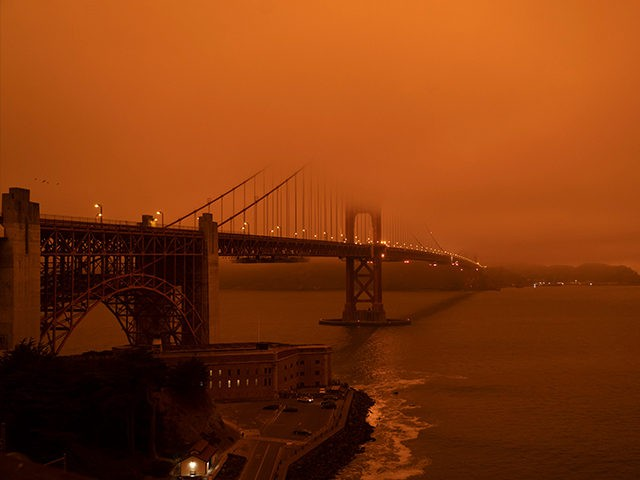"Cars drive along the Golden Gate Bridge under an orange smoke filled sky at midday in San Francisco, California on September 9, 2020. - More than 300,000 acres are burning across the northwestern state including 35 major wildfires, with at least five towns ""substantially destroyed"" and mass evacuations taking place. …"