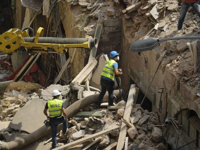 Rescue workers prepare to use a tube to vacuum debris from a badly damaged building in Lebanon's capital Beirut, in search of possible survivors from a mega-blast at the adjacent port one month ago, after scanners detected a pulse, on September 4, 2020. - Lebanese rescuers scoured rubble for a …