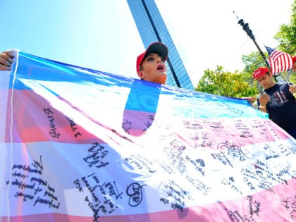 "Christen Greczowski, a transgender person, holds up a flag signed by transgender people who have left the Democratic Party, during the ""Straight Pride"" parade in Boston, on August 31, 2019. - ""Straight Pride"" advocates who support President Donald Trump and counter-demonstrators who consider them homophobic extremists staged dueling rallies in …"