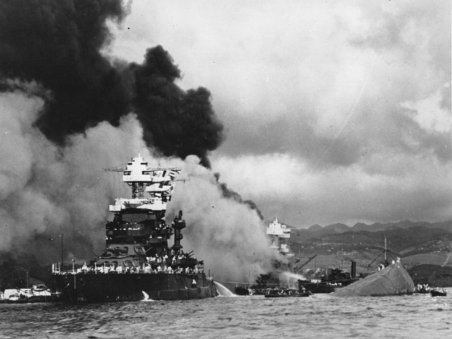 FILE - In this Dec. 7, 1941, file photo, part of the hull of the capsized USS Oklahoma is seen at right as the battleship USS West Virginia, center, begins to sink after suffering heavy damage, while the USS Maryland, left, is still afloat in Pearl Harbor, Oahu, Hawaii. Floyd …