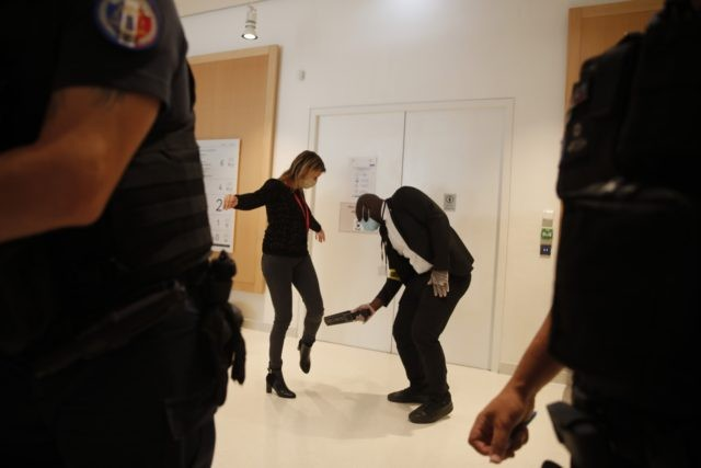 A woman is being scanned outside the courtroom before the 2015 attacks trial, Wednesday, Sept. 2, 2020 in Paris. Thirteen men and a woman go on trial Wednesday over the 2015 attacks against a satirical newspaper and a kosher supermarket in Paris that marked the beginning of a wave of …