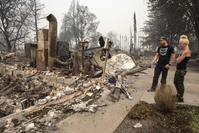 Derek Trenton and Shawna Haptonstall look at the ruins of Derek's parents home as wildfires devastate the region, Friday, Sept. 11, 2020 in Talent, Ore. (AP Photo/Paula Bronstein)
