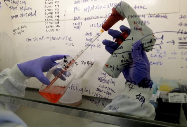 """In this July 30, 2020 photo, Kai Hu, a research associate transfers medium to cells, in the laboratory at Imperial College in London. Imperial College is working on the development of a COVID-19 vaccine. In a report to Congress and an accompanying """"playbook"""" for states and localities, key federal health …"""
